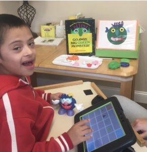 A child smiles at the camera. His speech generating device is on the table in front of him along with a toy monster.