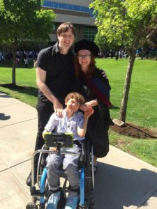 Bolin, dressed in graduation robes and hood, and her fiancé, Bryan Peterson, smile and pose outside with her son, Finnegan Bolin, a curly-haired pre-teen seated in a wheelchair with an adaptive pole holding his communication device.
