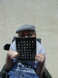 Michael Williams peering over his light-tech alphabet board.