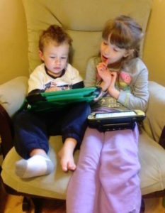 Maya and her brother, Will, are both sitting in a chair together. Each child has a communication system in his or her lap and Maya is watching Will constructing a message on his device.