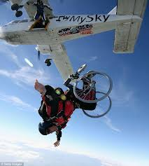 An individual in a wheelchair skydives out of an airplane.