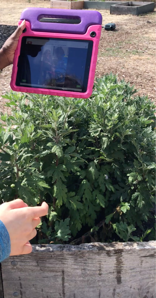 A child's left hand is holding up an iPad showing a video of gardening. The child is standing in front of a large planter.