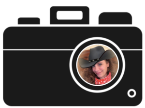 Black and white clipart image of a camera with photo of Lauren Enders smiling within the lens. The photo was created using with live photo filter app to add a black cowboy hat on her head and red bandana around her neck and change her eye color to blue.