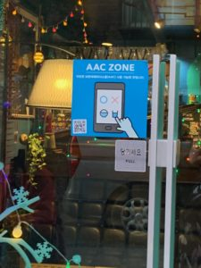 A picture on the front door of the coffee shop in South Korea. On the door is a sticker which indicates that the shop is part of the AAC zone.